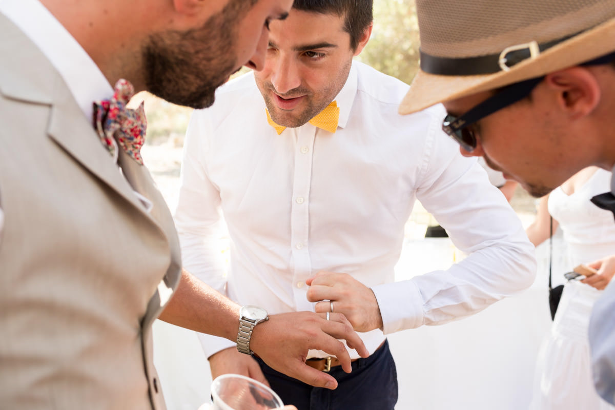 happy grooms show their wedding rings