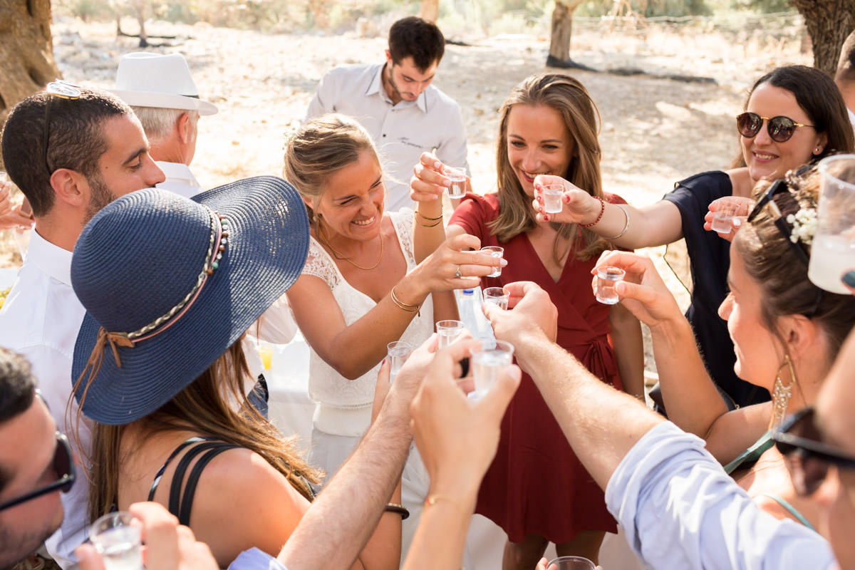 cheerful cretan wedding drinking raki